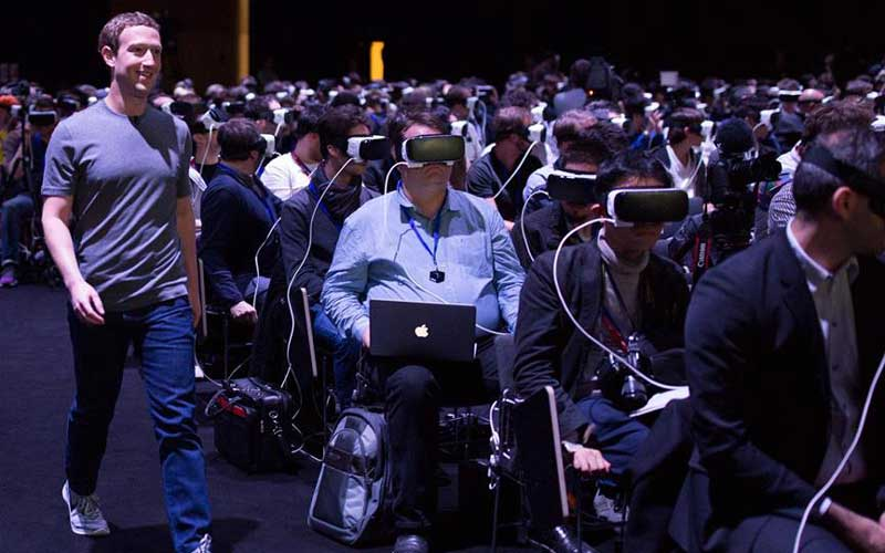 Mark Zuckerberg at the Mobile World Congress, walking past his audience all watching the same video in VR.
